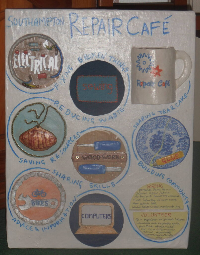 3D Information board describing repair cafe -images of electrical wiring, sewing, jewellery, woodworking, gluing, bike spanners, computer screen and cuppa